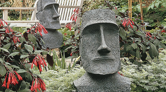 Moai's shown in a garden